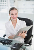 Happy businesswoman writing on clipboard sitting at desk — Stockfoto