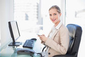 Cheerful blonde businesswoman text messaging — Stock Photo