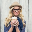 Pensive fashionable blonde holding coffee outdoors — Stock Photo #33421707