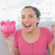 Smiling woman sitting on sofa and holding piggy bank — Stock Photo