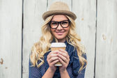Cheerful fashionable blonde holding coffee outdoors — Stock Photo