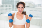 Sporty brunette lifting dumbbells looking at camera — Stock Photo