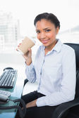 Amused young businesswoman drinking coffee — Stock Photo
