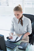 Blonde stern businesswoman writing in diary — Stock Photo