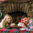 Couple with tea cups in front of lit fireplace — Stock Photo #36258147