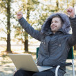 Cheerful man in fur hood jacket with laptop clenching fists in f — Stock Photo #36258509