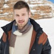 Man in warm clothing standing on snow covered landscape — Stock Photo