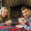 Smiling couple with tea cups in front of lit fireplace — Stock Photo #36258587