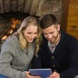 Lovely couple using tablet PC in front of lit fireplace — Stock Photo #36258795