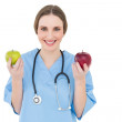 Stock Photo: Young woman doctor holding two apples