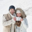 Couple in warm clothing with coffee cups on snowed landscape — Stock Photo