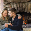 Romantic couple in front of lit fireplace — Stock Photo #36259027