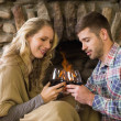 Couple toasting wineglasses in front of lit fireplace — Stock Photo #36259163