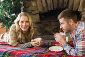 Yanan şömine önünde çay bardağı ile gülümseyen Çift — Stok fotoğraf