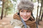 Woman in fur hat with woolen scarf in the woods — Stock Photo