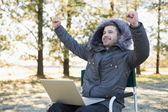 Cheerful man in fur hood jacket with laptop clenching fists in f — Stock Photo