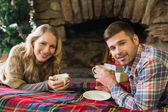 Smiling couple with tea cups in front of lit fireplace — Stock Photo