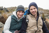 Smiling couple sitting on rock while on a hike — Stock Photo