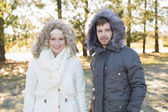 Smiling couple in fur hood jackets in the woods — Stockfoto