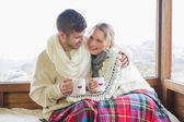 Loving couple in winter wear with cups against window — Stok fotoğraf