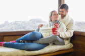 Loving couple in winter wear with cups against cabin window — Stock Photo