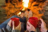 Hands with red coffee cups in front of lit fireplace — Stock Photo