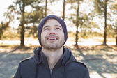 Smiling man in warm clothing looking up in forest — Stockfoto