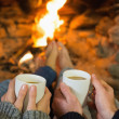 Hands holding coffee cups in front of lit fireplace — Stock Photo