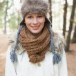 Woman wearing fur hat with woolen scarf and jacket in woods — Zdjęcie stockowe