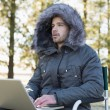 Young man in fur hood jacket using laptop in forest — Stock Photo #36261717