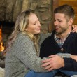 Lovely couple in front of lit fireplace — Stock Photo