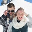 Happy couple in warm clothing in front of snowed hill — Stock Photo
