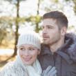 Smiling couple in winter clothing in the woods — Stok fotoğraf