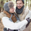 Couple in winter clothing embracing in the woods — Stock Photo #36263679