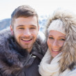 Loving couple in jackets against snowed mountain — Stock Photo