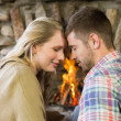 Stock Photo: Romantic couple with eyes closed in front of fireplace