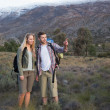 Stock Photo: Fit young couple with backpacks on landscape