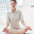 Smart businesswoman sitting in lotus position at office — Stock Photo #36264177