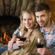 Couple with wineglasses in front of lit fireplace — Stock Photo #36264293