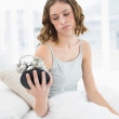 Upset woman holding an alarm clock looking at it sitting on her bed — Photo