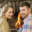 Smiling young couple in front of lit fireplace — Stock Photo #36264943
