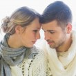 Loving couple in winter clothing against bright background — Stock Photo