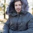 Young man in fur hood jacket using laptop in the forest — Stock Photo