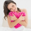 Cute woman hugging heart shaped pillow in bed — Stock Photo