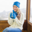 Cute woman with cup sitting in warm clothing against window — Stock Photo