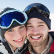 Close-up of a cheerful couple with ski goggles on snow — Stock Photo