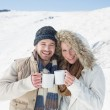 Cheerful couple in warm clothing with coffee cups on snowed land — Stock Photo