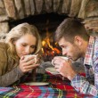 Romantic couple drinking tea in front of lit fireplace — Stock Photo