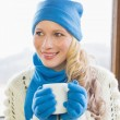 Woman with coffee cup in warm clothing against window — Stock Photo