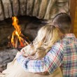Romantic couple sitting in front of lit fireplace — Stock Photo #36267747